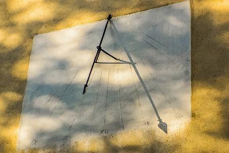 photo d'un cadran solaire basique sur un mur jaune